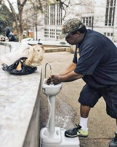 Homeless man uses new portable hand washing station
